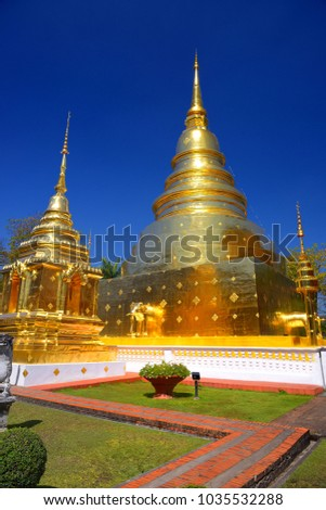 Wat Phra Sing WaramahavihanTemple with beautiful golden Stupa and blue sky background, Chiang Mai, Thailand. #1035532288