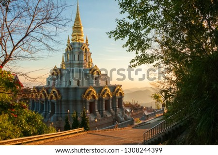 Wat Santikhiri Temple in Doi Mae Salong in Northern Thailand at beautiful warm sunrise light with mist in the mountains at the background #1308244399