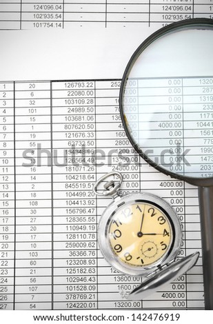 Watch and a magnifier on documents.