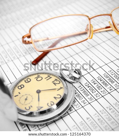 Watch and glasses on documents.
