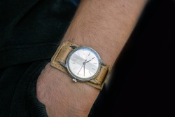 Watch brand new/vintage wristwatch  with round shape old leather strap on man hands with back background