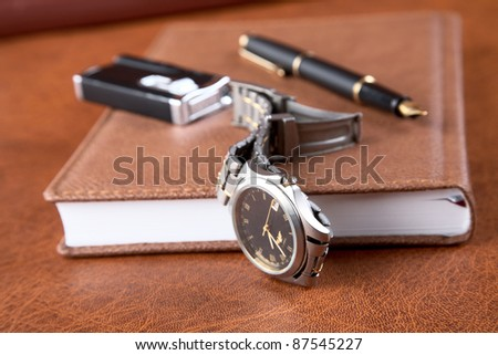 watch lighter  pen and an organizer on a textural background