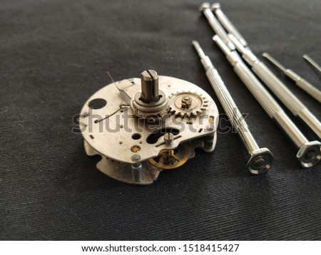 watch mechanism. clockwork mechanism and small screwdrivers