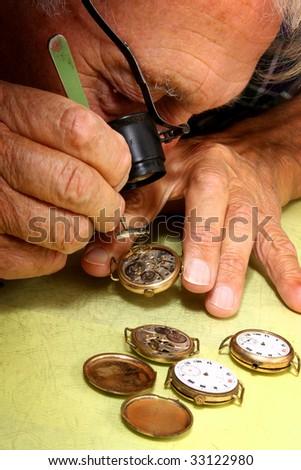 watch repair craftsman repairing old watch with tweezer