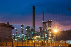 Watch the shadow of petrochemical plants and steel refineries, natural gas storage tanks at the back of the blue sky at dusk.