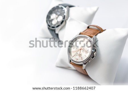 Watches white dial and brown stitched watch leather on a white background. Selective focus. Horizontal image.