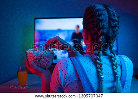 Watching a movie with popcorn, colorful colored background. Movies, movies