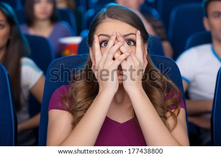 Watching a scary movie. Shocked young woman covering face with hands and watching movie while sitting at the cinema