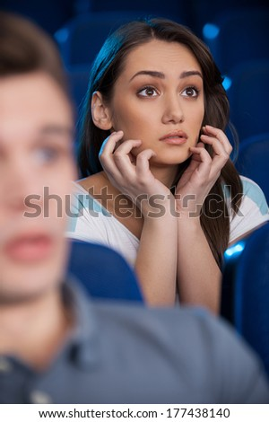 Watching an exciting movie. Excited young woman holding hands on chin while watching movie at the cinema