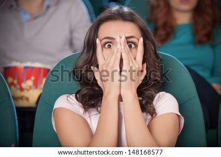 Watching  horror movie. Terrified young women covering her face with hand while watching movie at the cinema