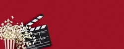 Watching movie with popcorn and clapperboard on red background. Movie goers accessories, cinematography concept. Long wide banner with copy space