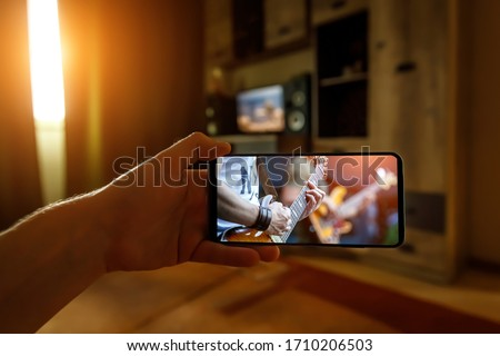 Photo of  Watching online music concert at home using a mobile phone. Guitar close-up on the screen