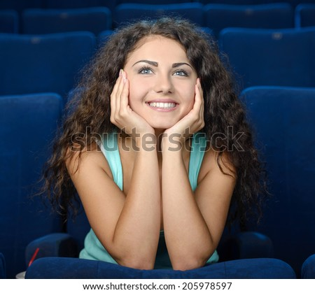Watching romantic movie. Thoughtful young women watching movie at the cinema