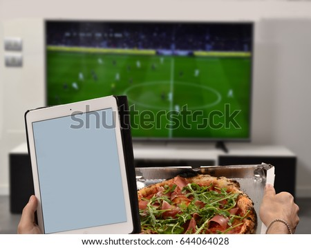 Watching television eating pizza and holding computer tablet.