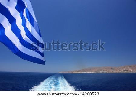 Watching the ship wake and the Greek flag (and the Greek island of Tinos in the far)