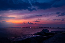 Watching the sunset on Breezy Point Beach on the end of one summer warm day. Dramatic cloudy dark blue sky and orange purple touch of the sun in the background. Big rocks in the foreground.