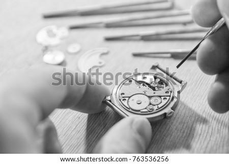watchmaker is repairing a...