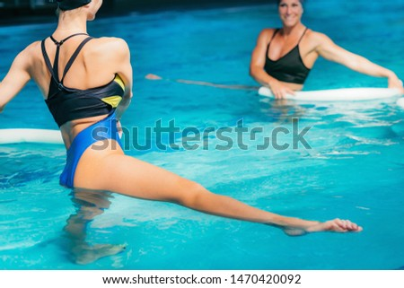 Water Aerobics Class, Group of Women Exercising with Instructor