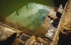 water and buildings in an old roman bath in the city of Bath in the united kingdom