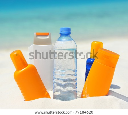 water and sun protection cream on beach background - stock photo
