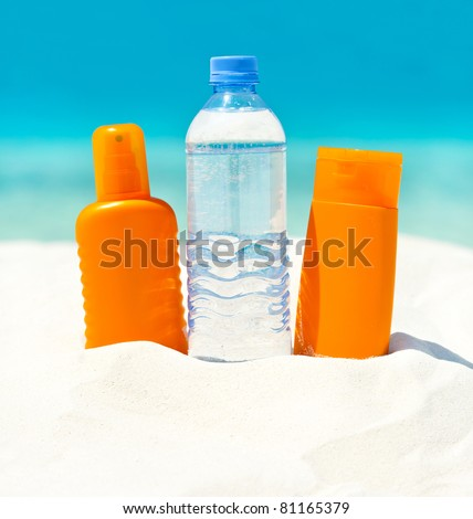 water and sun protection cream on sand beach background
