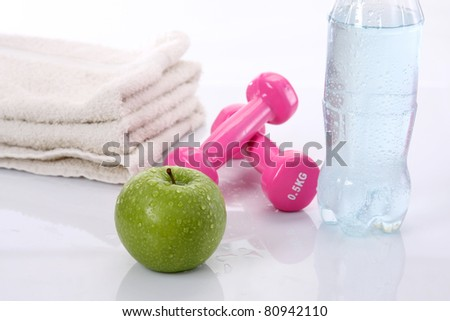 Water, apple, towel and dumbells isolated on white background