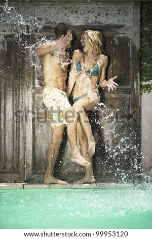 Water being splashed onto a young couple in swimwear by a swimming pool.