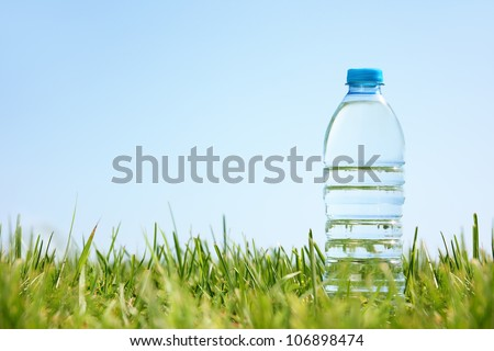 Water bottle on green grass with copy space. - stock photo
