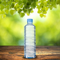 Water bottle on wood table with summer scene background