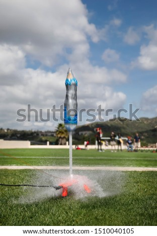 Water bottle rocket launch with rocket blurred from speed. Children out of focus in background on blue sky cloud backgound #1510040105