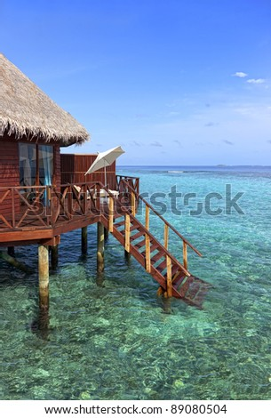 Water bungalow on tropical island with steps down into blue ocean. ideal travel background.