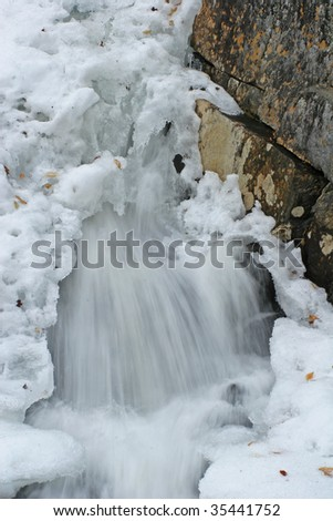 water bursting through snow pack down waterfall in winter