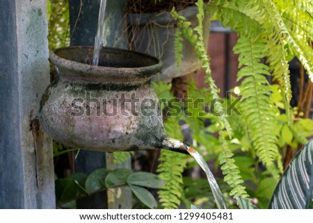 Water cascade from pots on pillar with flowing water in a tropical garden, Thailand. Garden water fountain featuring