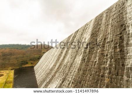 Water cascades down the Derwent Dam, Ladybower reservoir. Near Sheffield, in Peak District, Derbyshire, England, United Kingdom. #1141497896