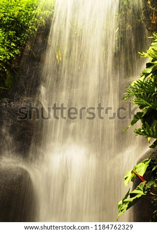 Water cascades rapidly onto rocks in this tropical waterfall. #1184762329