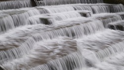 Water Cascading over Weir Step in river canal showing white water sharp and blurry