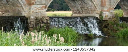 Water cascading under a stone bridge #1243537042
