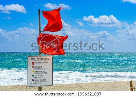 Water Closed to Public dual red warning flags and informational sign in front of rough, choppy ocean - Dania Beach, Florida, USA Zdjęcia stock ©