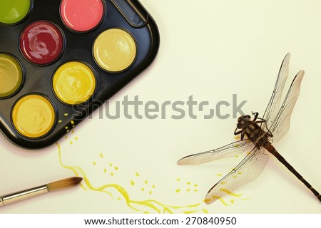 Water color paint set with a brush and a dragonfly as if he has walked through the paint with a grey background #270840950