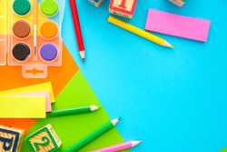 water color,plastic toy block,clipper,pin,note paper,pencils on colorful background.flat lay, top view.back to school concept