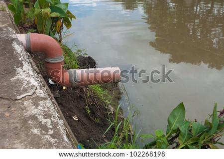 water coming out of a small pipe flowing into a river