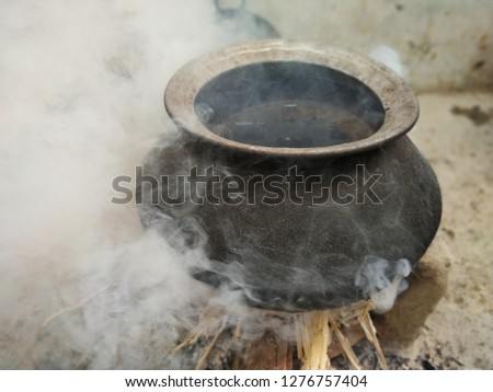 water container handi on fire , boiling water. smoke and fire
