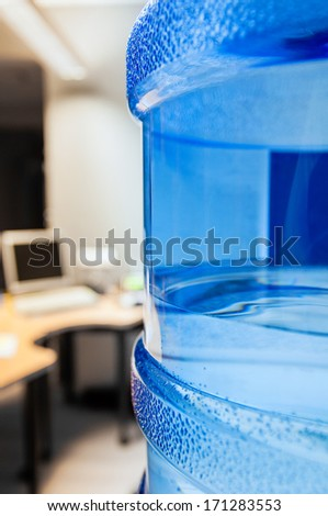 Water cooler with fresh water as seen in a modern office with computers in the background