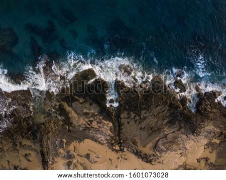 Water crashing into the shoreline of a beach.