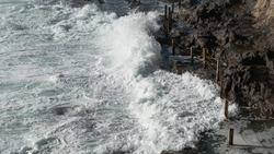 Water crashing on shoreline dangerous for bystander dramatic scene