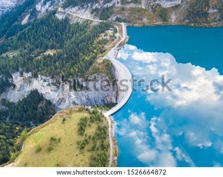 Photo of  Water dam and reservoir lake in Swiss Alps to produce hydropower, hydroelectricity generation, renewable energy, aerial drone photography