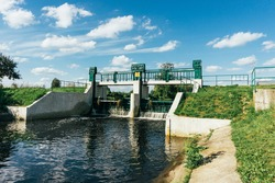 Water dam on a river. Water level regulation. Environment industry background. Summer draught low water level.