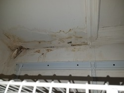 water damage in ceiling of closet with metal shelf