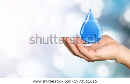 Water Day or World Oceans Day concept. Drop in human hand.