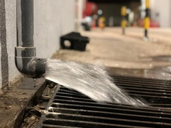 Water discharge or water drain from industrial manufacturing, out of focus, noise and grain effects.